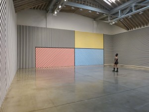 """Sol LeWitt, Wall Drawing #368:  The wall is divided vertically into five equal parts.  The center part is divided horizontally and vertically into four equal parts.  Within each part are three-inch (7.5 cm) wide parallel bands of lines in four directions in four colors.  In each of the other parts, three-inch (7.5 cm) bands of lines in one of the four directions.  The bands are drawn in color and India ink washes.  Red, yellow, blue, ink, India ink 3"""" (7.5 cm) bands.  First drawn by:  Jo Watanabe and others.  First installation:  Walker Art Center, Minneapolis, MN, January 1982. India ink. dimensions variable."""